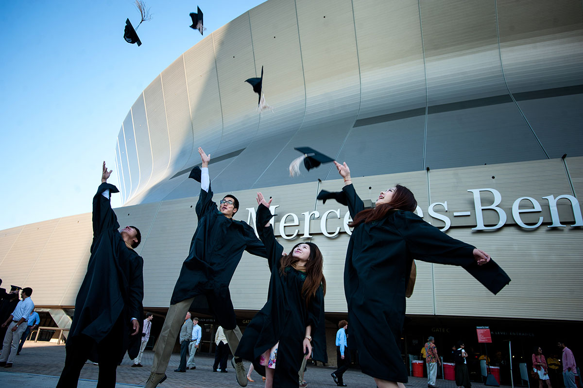 Four students jumping and tossing their graduation caps.