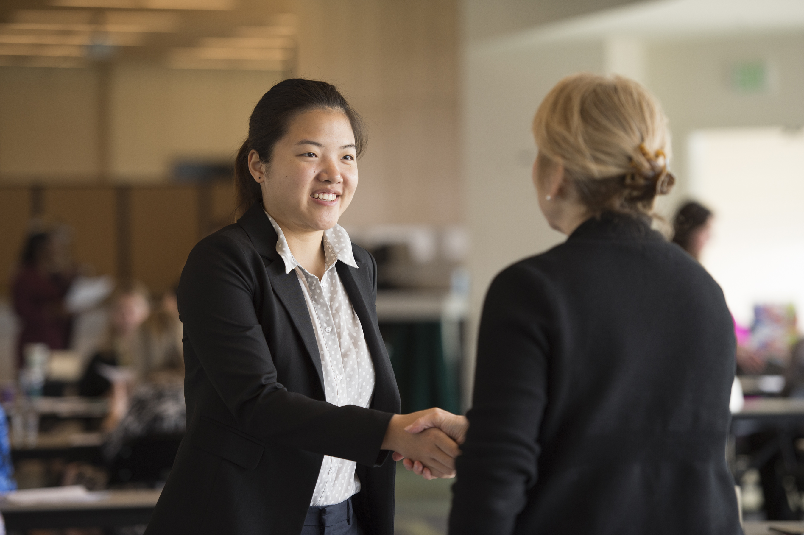 Student shaking hands with career coach.
