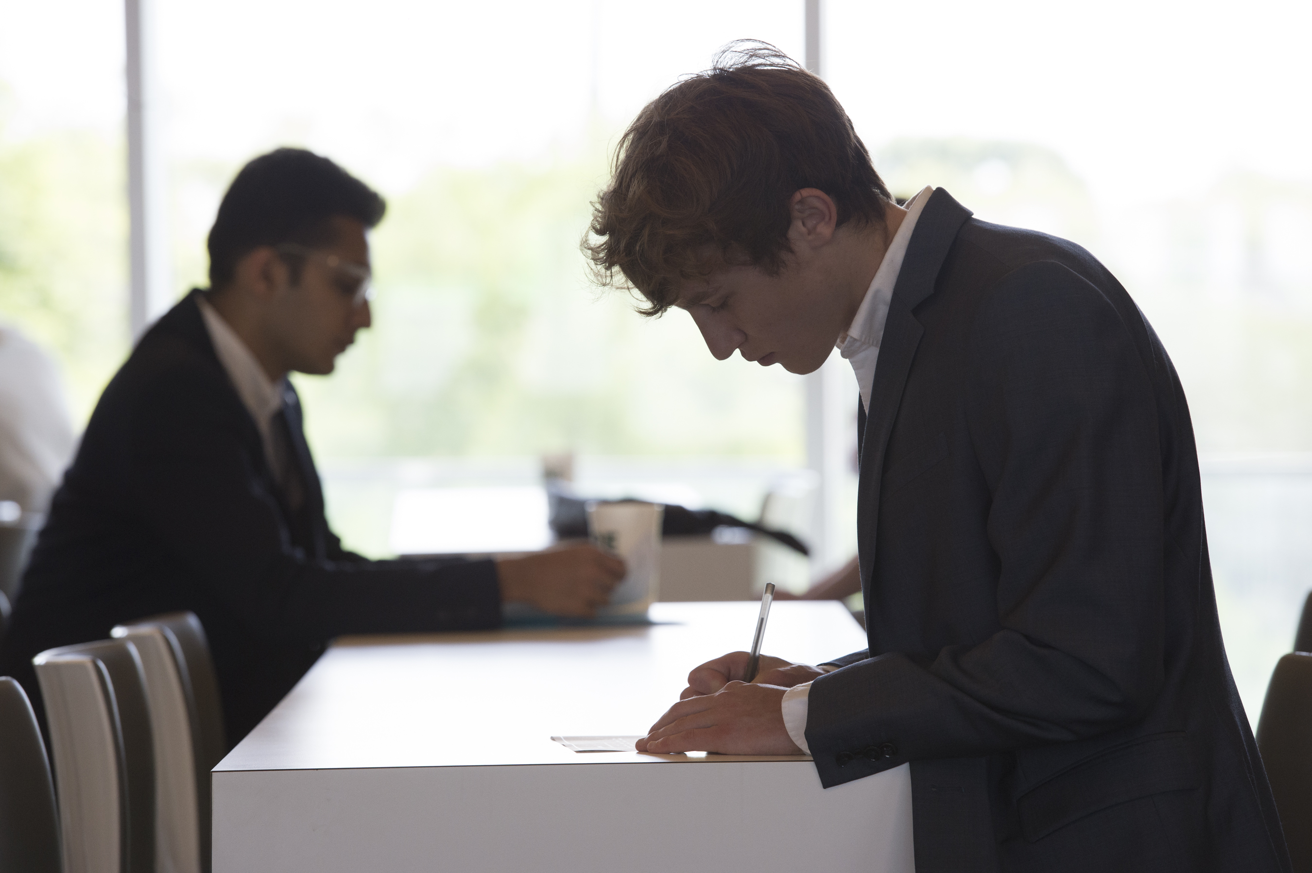 Two students in suits writing notes at a table.