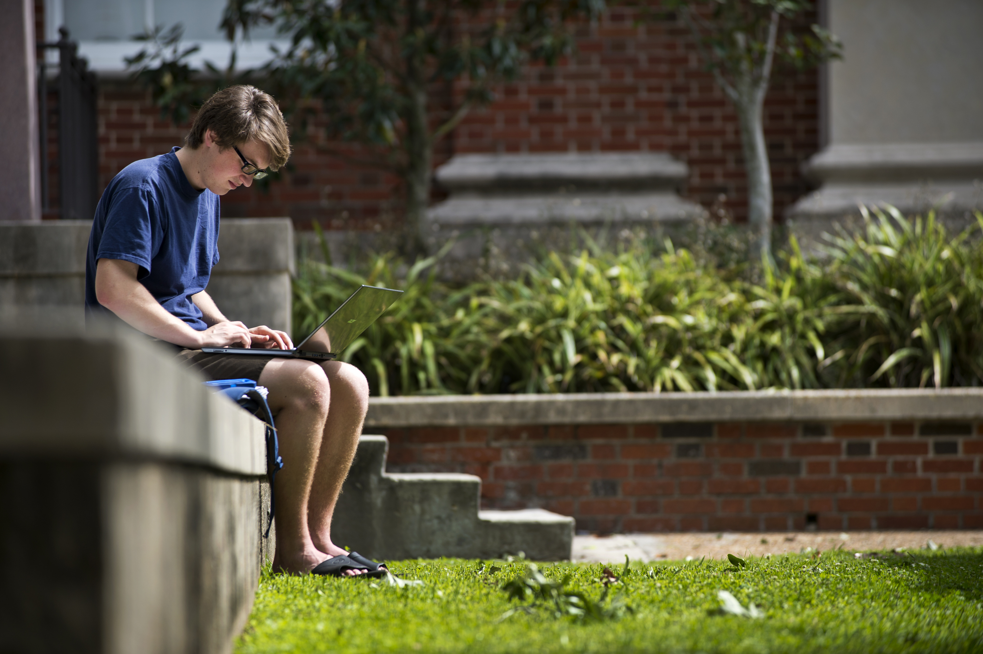Student sitting outside, typing on his laptop.