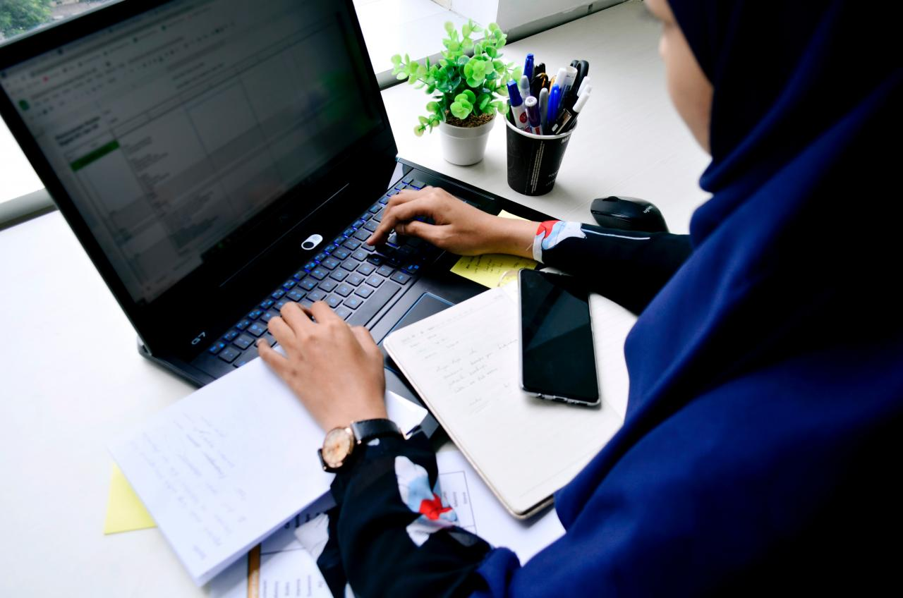 Woman in a hijab typing on a laptop at a desk.